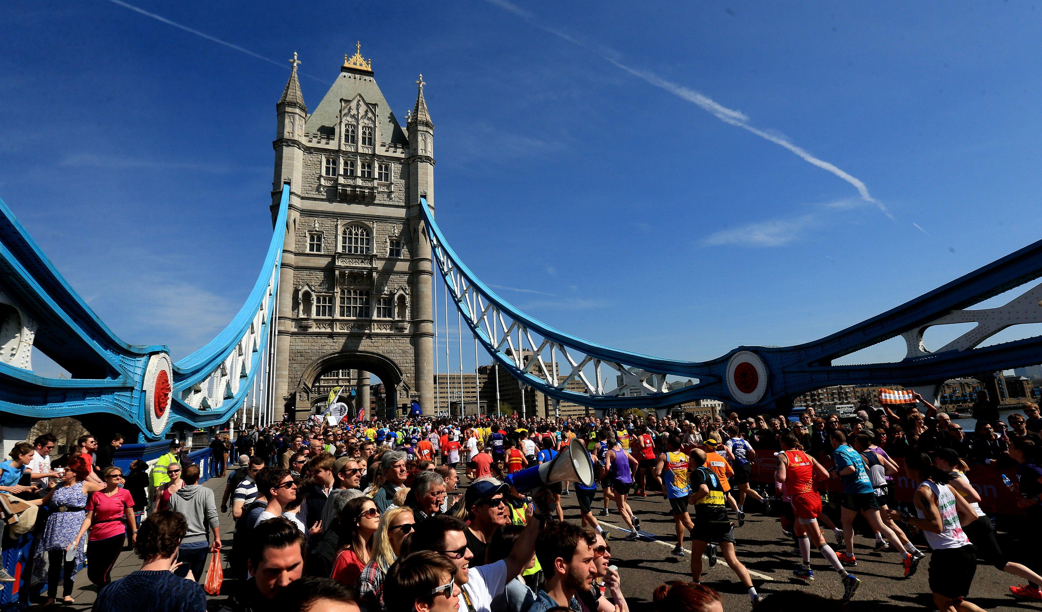 Spectators watch as runners cross Tower Bridge during the Virgin London Marathon in London.