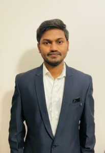 Image of editor Raju Kanukula. Raju is wearing a navy blazer with a white shirt with the top button open.