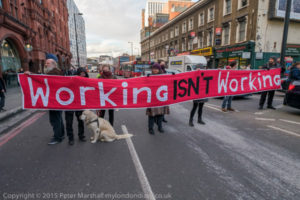 """London, UK. 4th March, 2016. Campaigners from the Mental Health Resistance Network and DPAC block traffic on the busy Old St round in portest against the use of Maximus job coaches in GP surgeries to """"create jobs by prescription."""" They say disabled people will be bullied into unsuitable work and lose benefits through sanctions. Peter Marshall/Alamy Live News"""