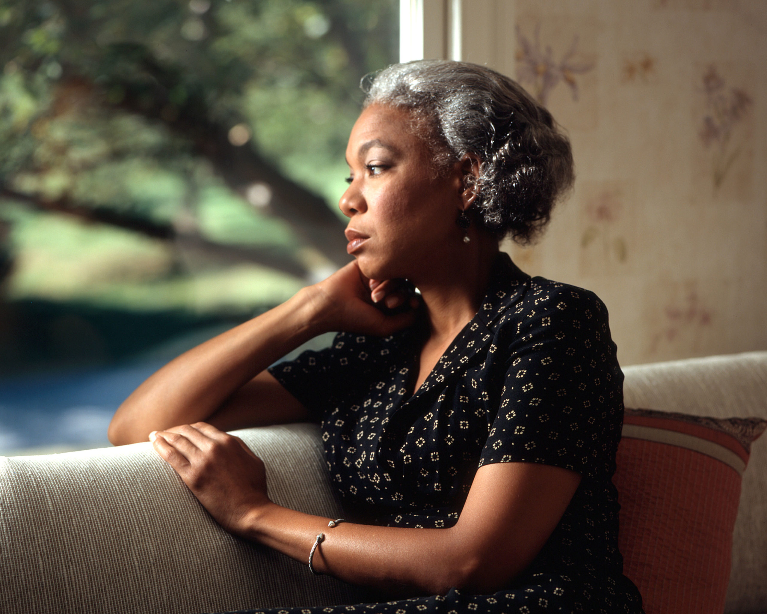 An African-American woman looking out a window