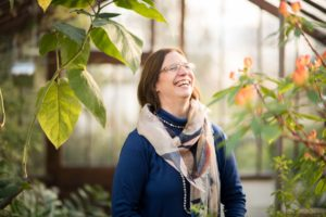 Giskin Day, with medium length brown hair, scarf and glasses, laughing in bright light. Botanical plants in the fore and background.
