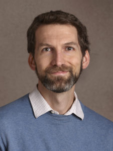 A headshot of the author, light brown hair and a trim beard. He wears a blue sweater and collared shirt, and smiles slightly.