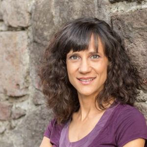 Image description for the alt text: Headshot of a white woman with olive complexion and curly brown hair. She stands against a rough stone wall and smiles slightly