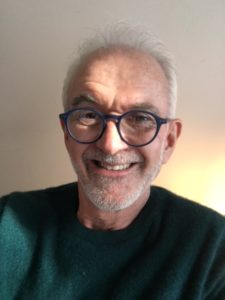 Headshot of Hugh, smiling in sunlight. He has a short gray beard and glasses, and wears a green shirt.