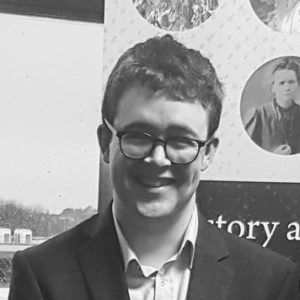 A black and white photo of David, smiling in sunshine. He wears glasses, short-cropped hair, and a collared shirt.