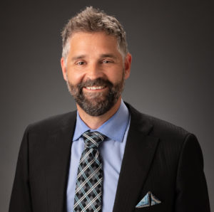 A headshot of Josh Mugele against a dark gray background. He wears a sportcoat and blue shirt with tie, has a beard and salt-and-pepper hair. He smiles at the camera.