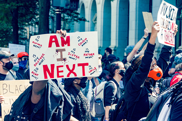 "Protestor holding a sign reading ""Am I Next""?"