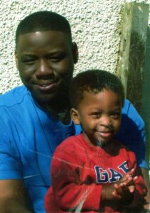Seni Lewis with a young child from his family